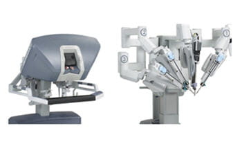 a gauche la machine qui permet au chirurgien de manipuler à distance les bras