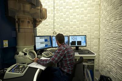 un opérateur, à l'intérieur d'une zone insonorisée, opère un microscope